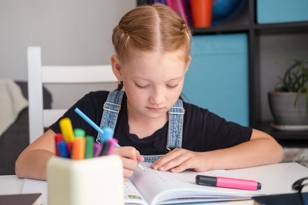 Portrait de jolie fille rousse caucasienne étudiant à la maison, concept d'éducation à distance. rédaction de devoirs. fermer. quarantaine. retour au concept de l'école.