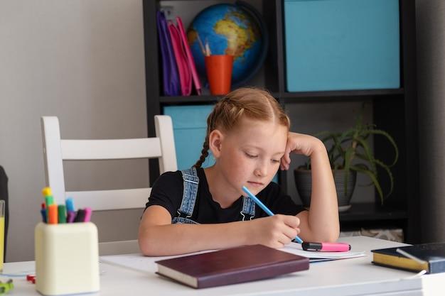 Portrait de jolie fille rousse caucasienne étudiant à la maison, concept d'éducation à distance. rédaction de devoirs. quarantaine. retour au concept de l'école.