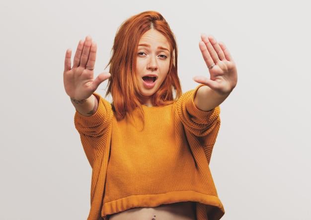 Portrait d'une jolie fille rousse faisant un geste d'arrêt