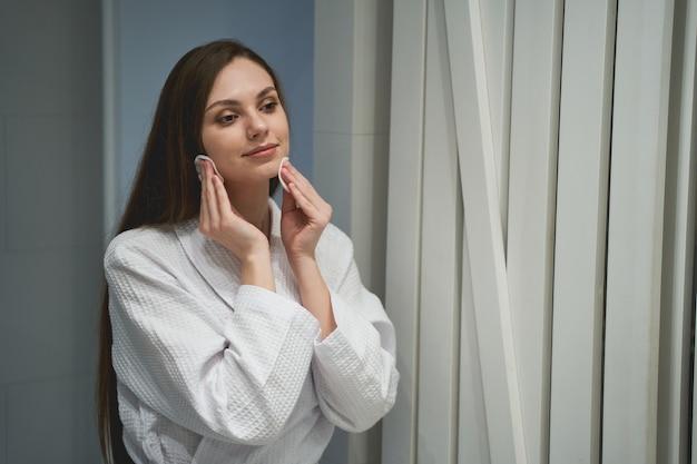Portrait d'une jolie fille sereine essuyant son maquillage devant le miroir