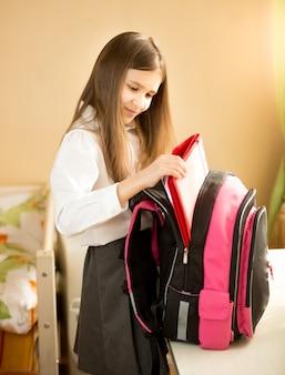 Portrait de jolie fille sortant des choses de son sac d'école