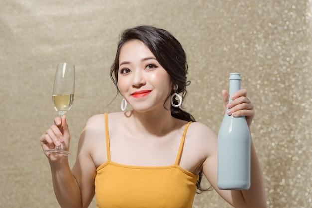 Portrait de jolie fille souriante dans les mains bouteille de champagne et verres à vin avec champagne.