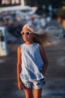 Portrait d'une jolie fille souriante de dix ans avec des lunettes. une fille en short et un t-shirt bleu au coucher du soleil près de la mer. turquie.