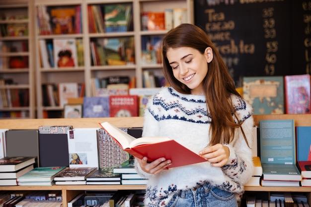 Portrait d'une jolie fille souriante lisant un livre à l'intérieur de la bibliothèque