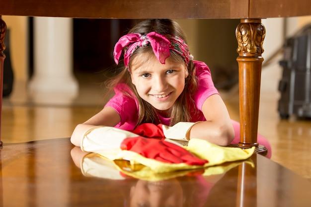 Portrait de jolie fille souriante polissant une table en bois avec un chiffon