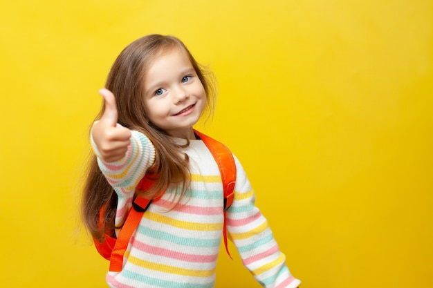 Portrait d'une jolie fille souriante avec un sac à dos européen retour à l'école thumbs up