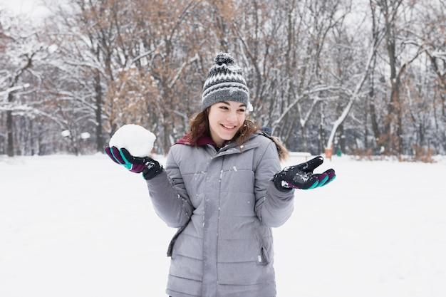 Portrait d'une jolie fille souriante tenant une boule de neige en forêt