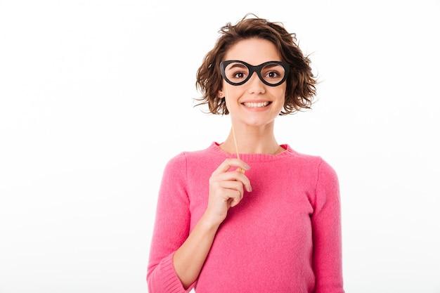 Portrait d'une jolie fille souriante tenant des lunettes en papier
