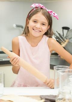 Portrait de jolie fille souriante tenant un rouleau à pâtisserie en bois tout en faisant de la pâte