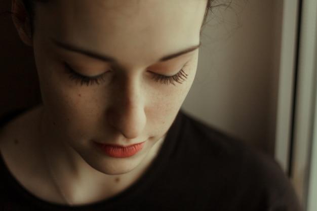 Portrait d'une jolie fille souriante, les yeux fermés et des taches de rousseur sur son visage