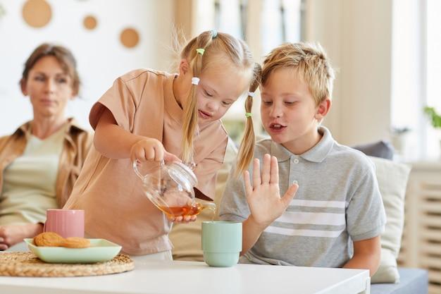 Portrait de jolie fille avec le syndrome de down poring thé dans une tasse tout en profitant du temps avec la famille à la maison, copiez l'espace