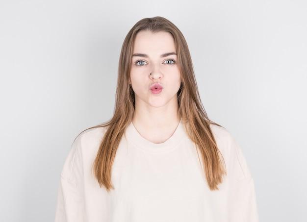 Portrait de jolie fille en tenue décontractée envoyant un baiser soufflant avec des lèvres moue regardant la caméra isolée sur fond blanc.