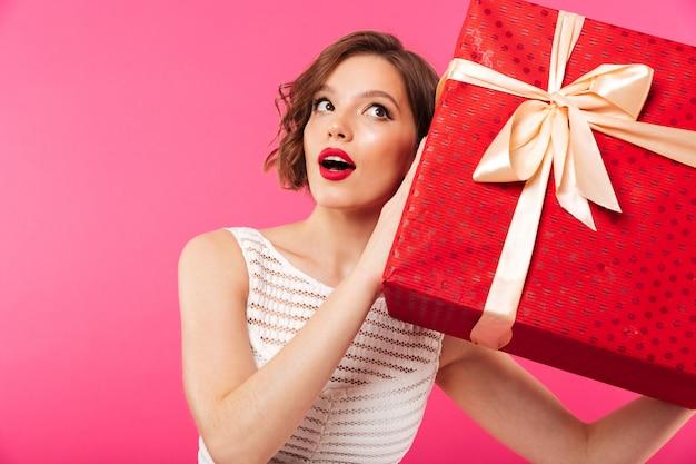 Portrait d'une jolie fille vêtue d'une robe tenant un cadeau