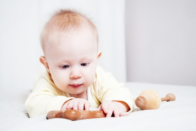 Portrait d'une jolie fillette de sept mois aux yeux bleus. un enfant joue avec des jouets en bois dans une pièce lumineuse. jouets écologiques pour enfants fabriqués à partir de matériaux naturels.
