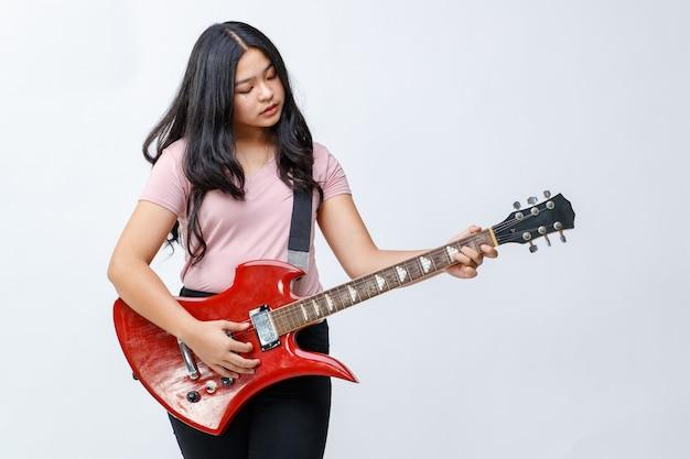 Portrait d'une jolie jeune adolescente tenant la guitare électrique. guitariste junior professionnel debout et jouant d'un instrument tout en regardant la caméra fond blanc isolé