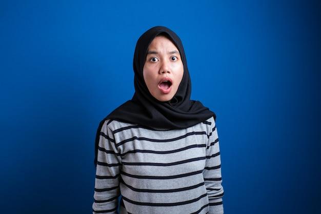 Portrait d'une jolie jeune étudiante musulmane asiatique portant le hijab montre une expression surprise ou choquée avec la bouche ouverte, gros plan sur une expression faciale heureuse sur fond bleu