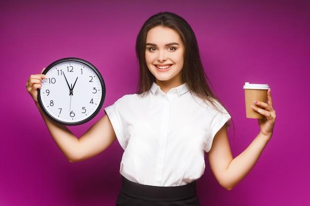 Portrait d'une jolie jeune femme d'affaires brune debout isolée sur violet, tenant une tasse de café.