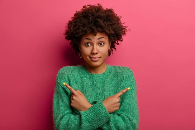 Portrait de jolie jeune femme afro-américaine hésitante croise les mains sur la poitrine