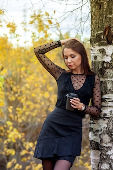 Portrait de jolie jeune femme d'apparence slave en robe sombre et verre de café à l'automne, debout à côté de bouleau sur fond d'un parc d'automne et étang avec de l'eau