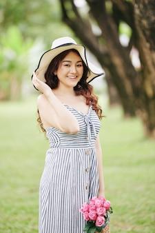 Portrait de jolie jeune femme asiatique au chapeau debout dans le parc de la ville avec panier de fleurs roses