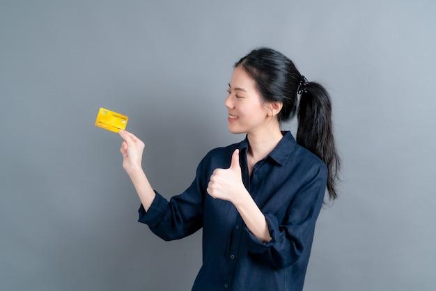 Portrait d'une jolie jeune femme asiatique montrant une carte de crédit avec espace de copie sur fond gris