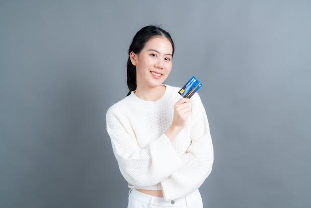 Portrait d'une jolie jeune femme asiatique en pull montrant une carte de crédit avec espace de copie sur fond gris