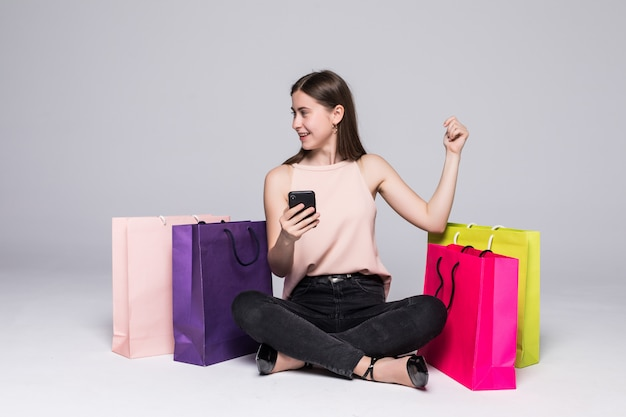 Portrait d'une jolie jeune femme assise sur un sol avec des sacs à provisions et à l'aide de téléphone portable avec geste de victoire sur mur gris