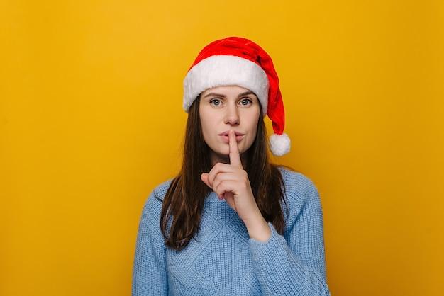 Portrait de jolie jeune femme au chapeau rouge de noël, fait un geste silencieux, habillé en pull bleu hiver, pose sur fond de studio jaune pastel. bonne année célébration joyeuses fêtes