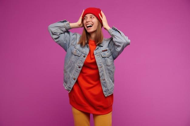Portrait de jolie jeune femme aux cheveux longs brune. porter une veste en jean, un pantalon jaune, un pull rouge et un chapeau. regarder vers la gauche à l'espace de copie, isolé sur mur violet