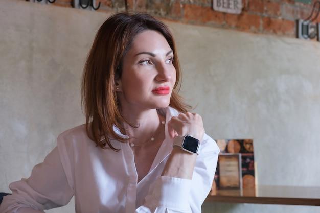 Portrait d'une jolie jeune femme aux cheveux rouges en chemise blanche à une table en bois dans un café. la femme repose sa tête avec sa main et regarde pensivement sur le côté.