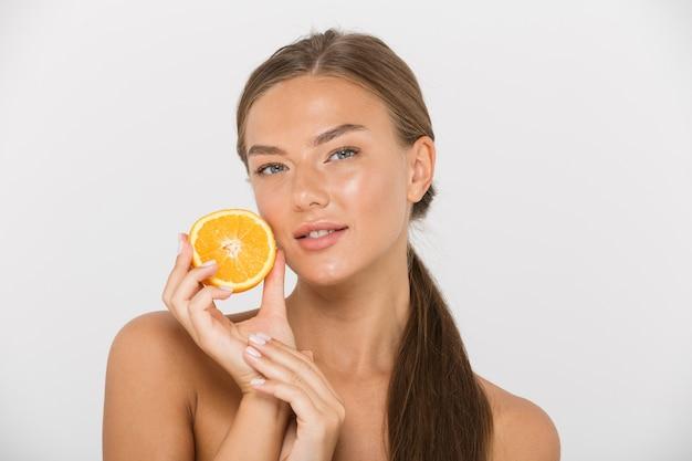 Portrait d'une jolie jeune femme aux seins nus isolée, montrant des tranches d'orange