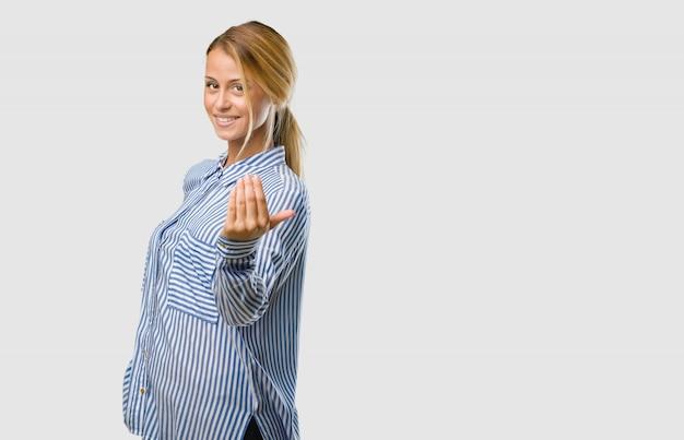 Portrait d'une jolie jeune femme blonde invitant à venir, confiante et souriante, faisant un geste avec la main