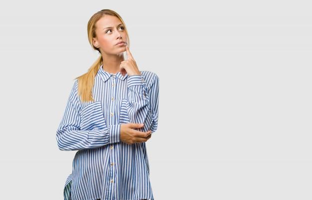 Portrait d'une jolie jeune femme blonde réfléchissant et levant les yeux, confuse à propos d'une idée