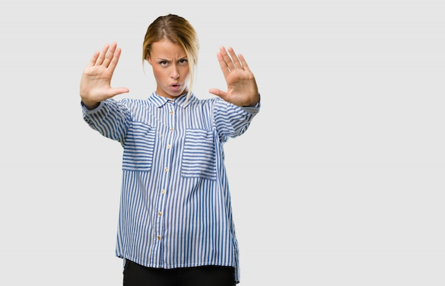 Portrait d'une jolie jeune femme blonde sérieuse et déterminée, mettant la main devant, arrêtez le geste