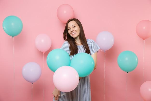 Portrait de jolie jeune femme brune heureuse souriante vêtue d'une robe bleue tenant des ballons à air colorés sur fond rose tendance lumineux. fête d'anniversaire, concept d'émotions sincères.