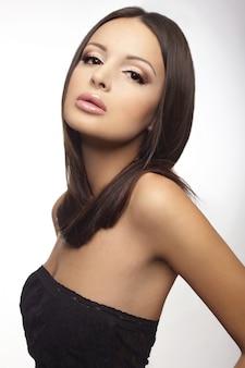 Portrait d'une jolie jeune femme brune isolée sur blanc