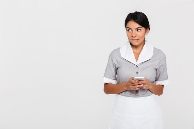 Portrait de jolie jeune femme brune en uniforme se mord une lèvre tout en utilisant le téléphone
