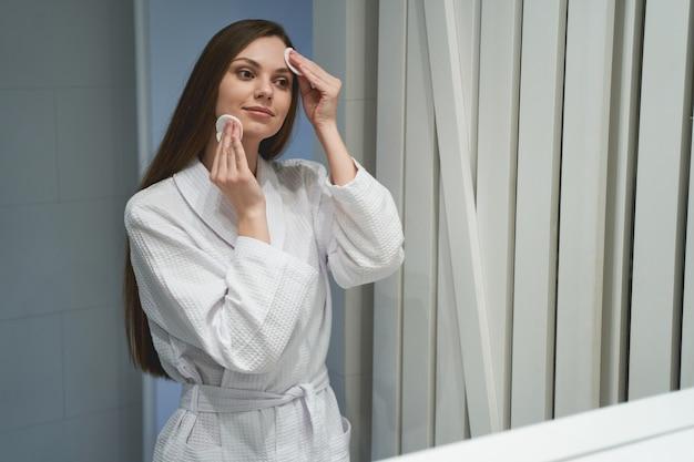 Portrait d'une jolie jeune femme caucasienne calme à l'aide de cotons pour un démaquillage