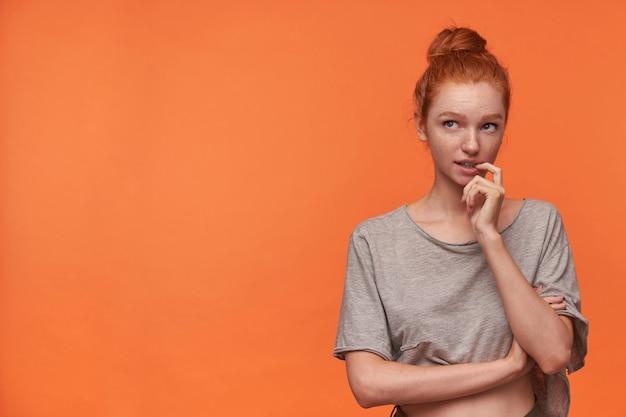 Portrait de jolie jeune femme avec une coiffure foxy bun portant un t-shirt gris et un short vert, debout sur fond orange, tenant l'index sur le dessous et regardant pensivement vers le haut