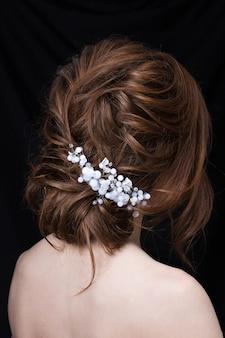 Portrait d'une jolie jeune femme avec une coiffure de mariage. vue arrière.