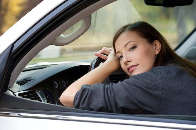 Portrait de jolie jeune femme dans la nouvelle voiture - à l'extérieur