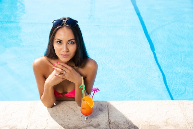 Portrait de jolie jeune femme debout dans la piscine à l'extérieur
