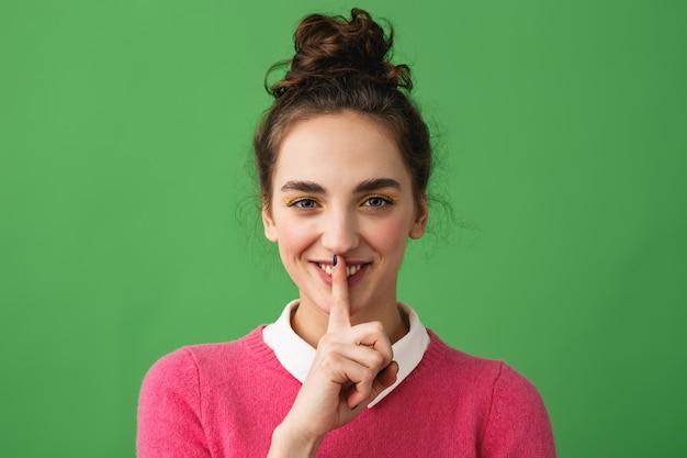 Portrait d'une jolie jeune femme debout isolée, montrant le geste de silence
