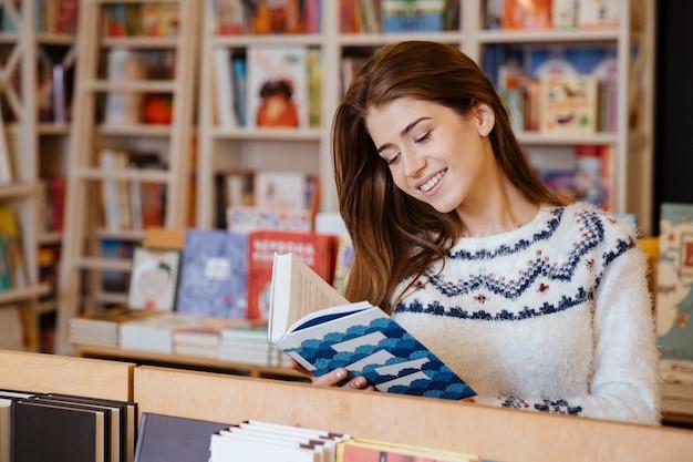 Portrait d'une jolie jeune femme debout et lisant un livre dans la bibliothèque