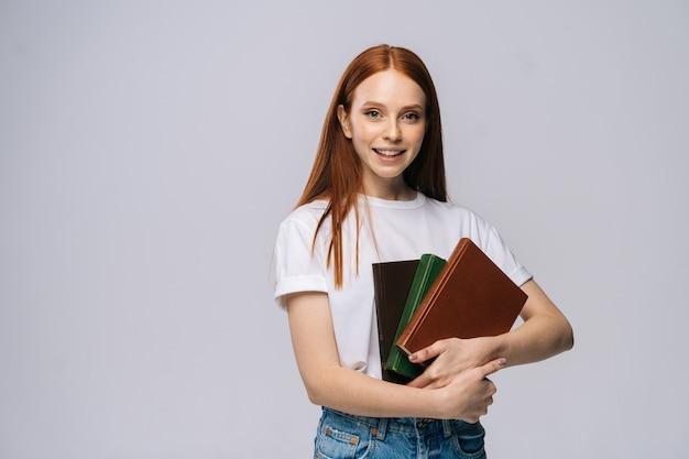 Portrait de jolie jeune femme étudiante tenant un livre et regardant la caméra