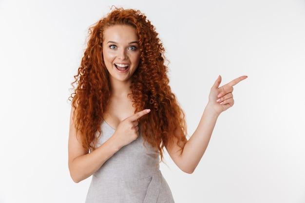Portrait d'une jolie jeune femme excitée avec de longs cheveux roux bouclés isolés, présentant un espace de copie, pointant
