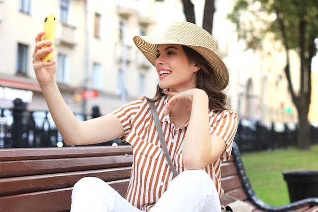 Portrait de jolie jeune femme faisant selfie par téléphone assis sur un banc dans la rue de la ville.