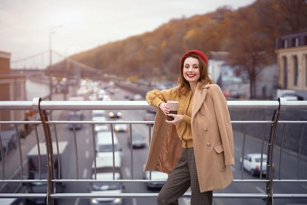 Portrait d'une jolie jeune femme française souriante regardant la caméra debout au pont piétonnier avec