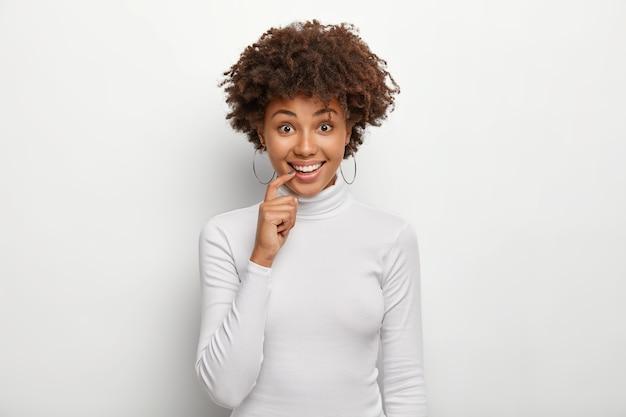 Portrait de jolie jeune femme garde l'index sur la lèvre inférieure, regarde avec plaisir, a une coiffure frisée, porte un pull poloneck