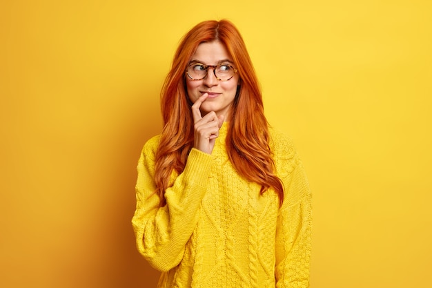 Portrait de jolie jeune femme heureuse garde l'index près des lèvres concentré de côté a une expression réfléchie a les cheveux roux naturels porte un pull décontracté.